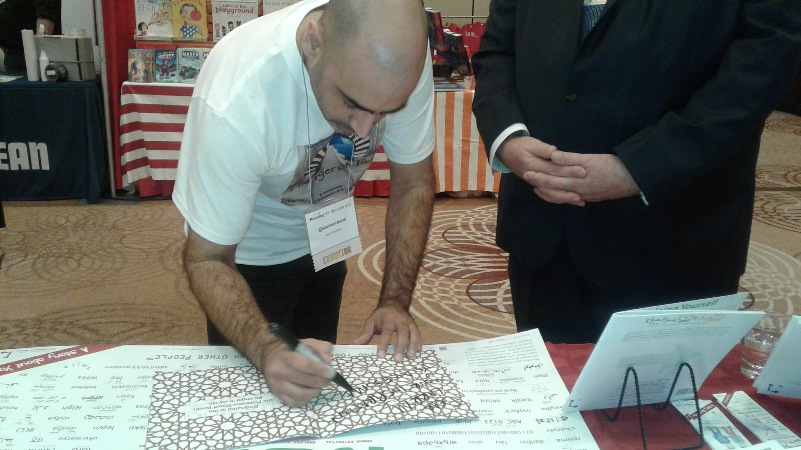 @studentAsim signs a copy of The Tyer of Ties at the book launch